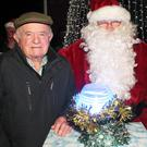 Santa switching on the Ballycanew lights helped by Harry and Evelyn Furney