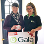 Mary receives her prize from a member of the Gala retail team