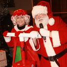 Santa Claus and Mrs Claus turning on the lights
