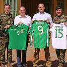 Minister Kehoe and Taoiseach Varadkar present Ireland jerseys worn by the players in a recent game to the troops courtesy of the FAI