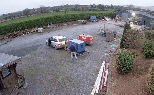 This CCTV image appears to show two men attaching the generator to the car
