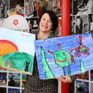 Bronagh Carron holding the works of12-year old Ceri Maguire entitled 'The Dogs of Germany' and 'Ollie The Octopus' by 6-year old John Redmond