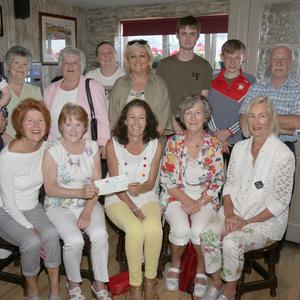 Margaret Walker presenting a cheque on behalf of family and friends who took part in sponsored walk at Enniscorthy Sports Hub to Maria Condon, Una Murphy and Mary O'Shea from Wexford Hospice Homecare in Dawsons Pub.