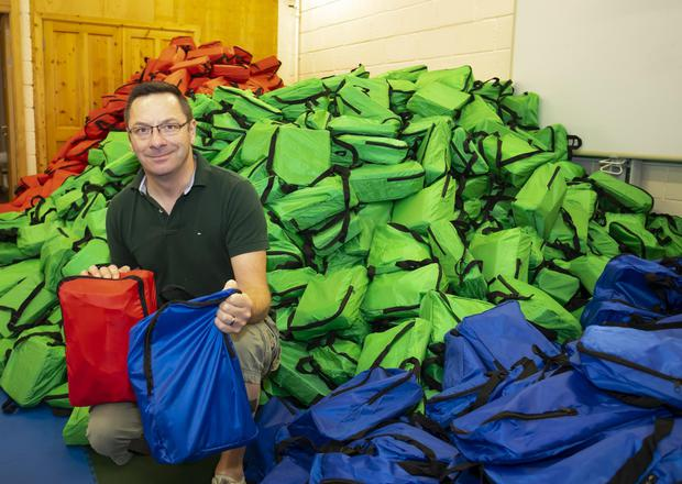 Cllr Michael Sheehan with a mountain of back-to-school kits ready to be delivered to families around the county