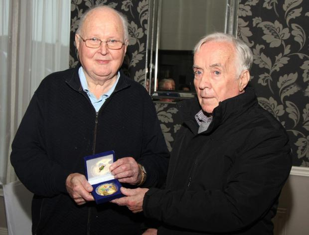 Sean Bissett, president of the Motorcycle Union of Ireland, presents Cyril with a gold lifetime achievement medal