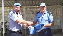 Garda Mick Dee and Inspector Pat Cody exchanging caps and berets during some down time in Cyprus