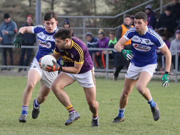 Wexford's Conor Devitt looks to get away from Brian Byrne and Robert Pigott of Laois