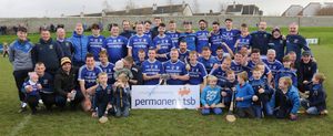 The Ballyhogue players, mentors and some of their young supporters with the spoils of victory