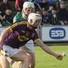Cathal Dunbar stoops to win the ball ahead of Offaly defender Paddy Delaney