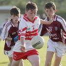 Dylan Nash of Ballinastragh Gaels about to kick after evading the twin challenge of St. Martin's duo Derry Crowley and Joe Mernagh