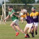 Paul Larrissy of Crossabeg-Ballymurn tries to hold off Pádraig Clancy as Paddy Glover (Faythe Harriers) looks on.