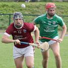 Ciarán Lyng of St. Martin's targets possession with Naomh Eanna's Conor Hughes in the background