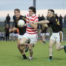 Patrick Breen of Ferns St. Aidan's finds the gap between Sean Barden and James Delaney of Adamstown.