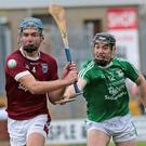Eoin Conroy of Naomh Eanna attempts the hook as Conor Firman (St. Martin's) prepares to clear