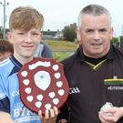 Eoin Staples, the St. Anne's captain, receives the shield from referee Brendan Martin