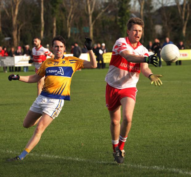 Richard Hughes of Kilanerin with the off-load as Raheen's Colm Power looks on