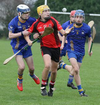 Declan Sinnott of Oulart-TheBallagh is closed down by Caleb Murphy and Jason Bolger (Ballinastragh Gaels).