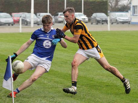 Niall Parker is close to the sideline as he clears the ball under pressure from Conor Hearne of Shelmaliers.