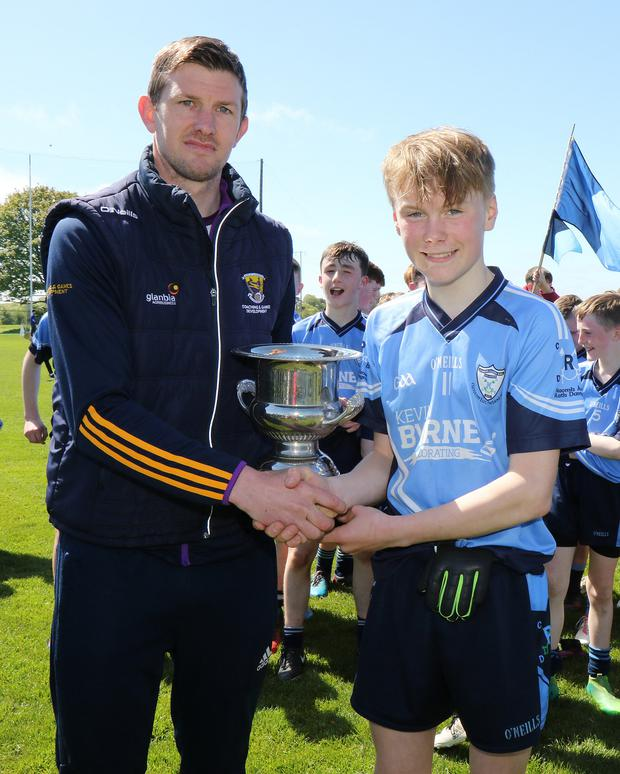 Cathal Murphy receives the trophy from Anthony Masterson