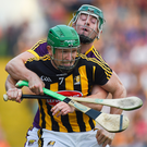 Kilkenny's Paul Murphy is wrapped up by Wexford substitute Harry Kehoe