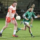 Jim Hughes of Kilanerin under pressure from Peter Travers of Naomh Eanna with referee John Carton in close proximity