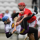 Wexford netminder Mark Fanning is heavily tackled by Cork captain Bill Cooper during Sunday's league tie in Páirc Uí Chaoimh