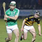 Gary Molloy of Naomh Eanna about to strike as Rathnure's Pádraig Doyle looks on