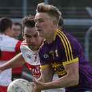 Martin O'Connor on the ball for Wexford as Benny Heron of Derry reduces his options