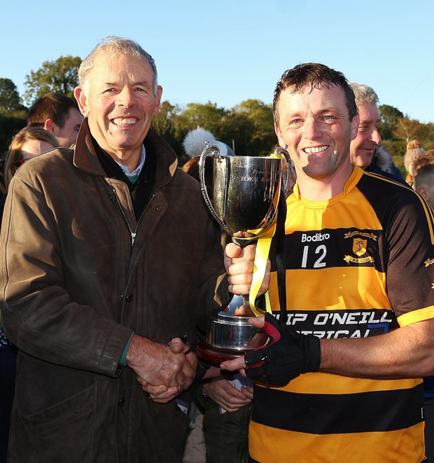 Nigel Higgins of Rathnure receives the trophy from Thos. Ryan