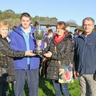 Kevin Bates of Good Counsel College accepts the Donna Foley Memorial Cup from Anna and Denise Foley, with Athletics Wexford Chairman Paddy Morgan looking on