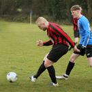 Joe Bolger of Gorey Rangers is tracked by James Fleming of Courtown Hibs