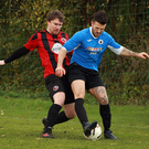 Glen Hughes of Courtown Hibs is challenged by Jonathan Savage of Gorey Rangers