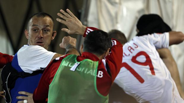 A Serbian national team supporter, left, fights members of the Albanian national soccer team the match between Serbia and Albania in Belgrade (AP)