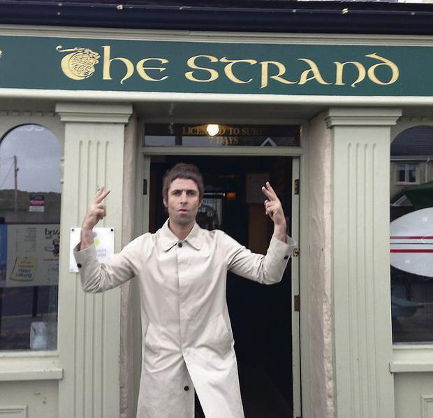 OFF TO THE PUB: Liam Gallagher hit by the weather in Sligo