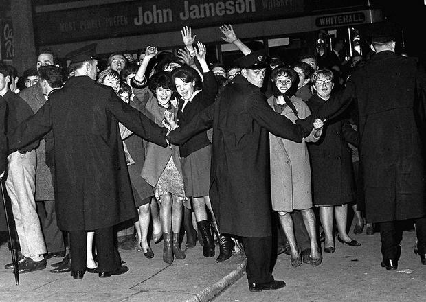 Police hold back the crowd waiting to get into the Beatles concert in Dublin