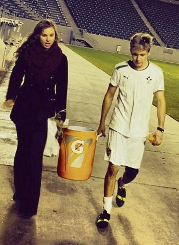 BALL GIRL: Niall leaves the pitch with mystery brunette and (right) after kick-about