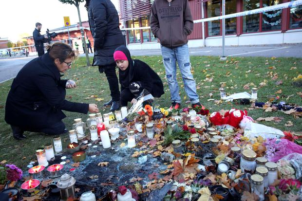 Mourners light candles outside Kronan school in Trollhattan, Sweden, Friday, Oct. 23, 2015, a day after an attack. The attacker who stabbed two people to death at the school before being shot and killed by police had a racist motive, police said. (Adam Ihse/TT News Agency via AP) SWEDEN OUT