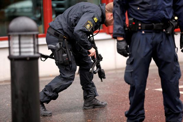 Police officers are seen at a school in Trollhattan, October 22, 2015. A masked man wielding