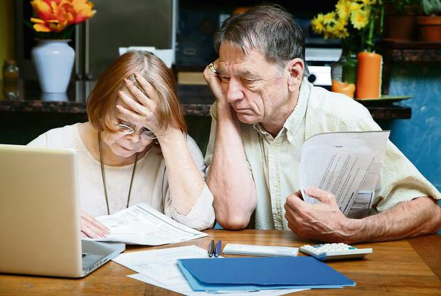 Senior couple at home reacting to many bills
