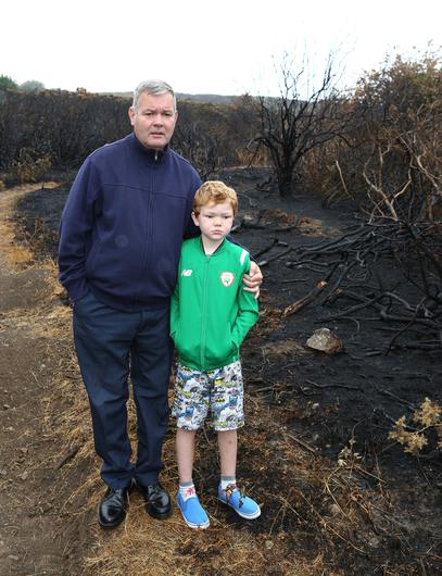 Cliff Road resident Jack Curran and son Declan amongst the scorched brush close to their home in Bray