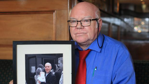 Brian Fetherston holding a photo of his tragic son Ken