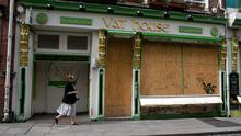 A woman walks past the Vat House pub which remains boarded up in Dublin city centre