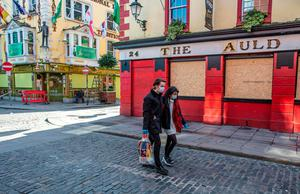 People wearing face mask as a precautionary measure against Covid-19, carry a shopping bag as the pass a boarded-up and temporarily closed pub in Dublin