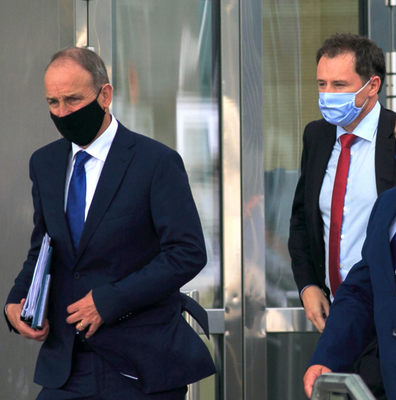 Wearing protective masks, Taoiseach Micheál Martin and Agriculture Minister Charlie McConalogue leave a session of the Dáil at the Convention Centre