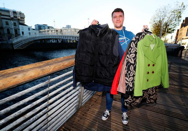 Paddy Fryers, 28, who runs the organisation called Warm for Winter, on the Ha'penny Bridge in Dublin's city centre, with some of the thousands of coats donated to help the city's most needy make it through this winter. PA Photo. Picture date: Friday November 6, 2020. See PA story IRISH Coats.