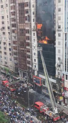 Flames leap from the windows of the 21-storey office building in Dhaka as firefighters try to tackle the blaze and reach people trapped inside