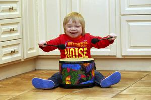 Jack McNiffe playing his drum in the kitchen of his family home