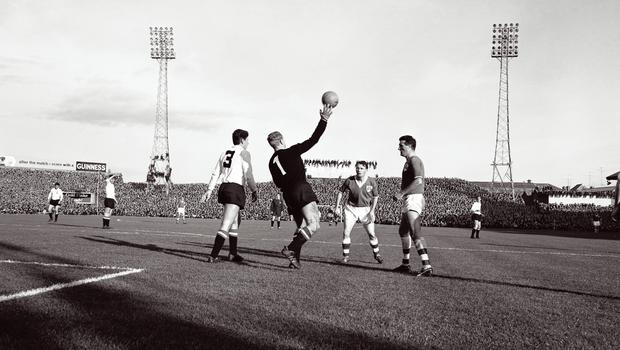 Ireland take on Austria in 1963, with some fans enjoying a bird's-eye view from ad hoardings and floodlights