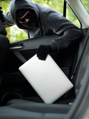 Thief breaking into car (stock)