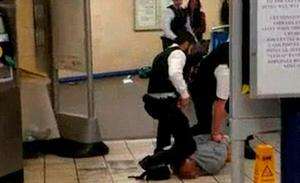 Police officers hold down the suspect at Leytonstone tube station